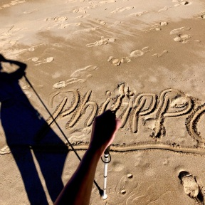 The image above is of a left hand holding a guide cane, looking down onto my name, Philippa, written in the sand. My shadow goes off to the left.