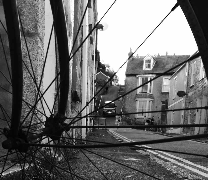 Black and white image: Looking throug bike spokes, up a side street. You can see a car in the distance coming down a steep hill.