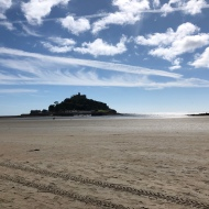 Looking out to Saint Michaels Mount Mount. The sky is blue wity white fluffy clouds.