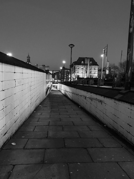 Shot on iPhone, in black and white. walking down the passageway which runs down the side of the train station. The walls are painted white and there is a row of lamps at street level. Saint Georges all, a theatre, is visible on the right hand side.