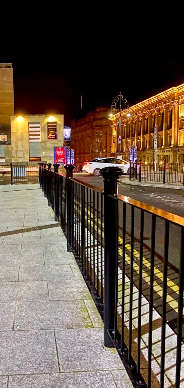 Stood at at a taxi rank outside Bradford Interchange. This image is in colour. There are railings on the right, with a white taxi on the top right hand side.