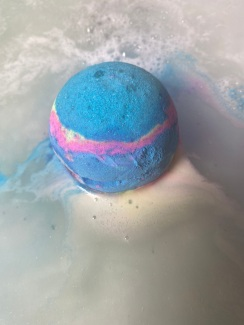 A blue bath bomb in the water, fizzing.