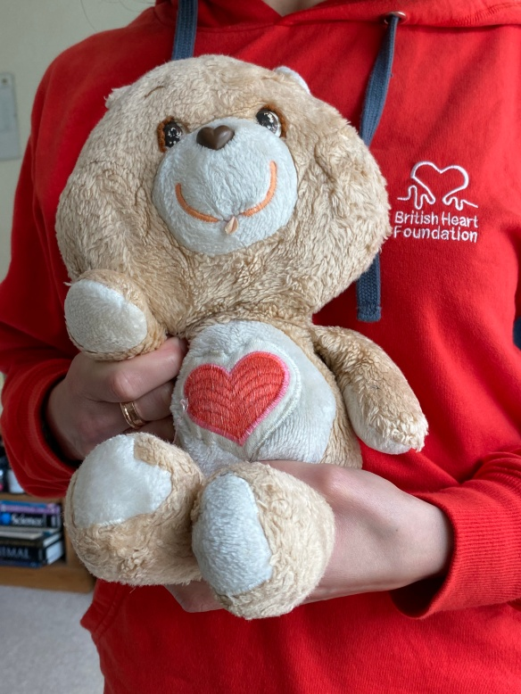 Me in a BHF hoodie, holding my bear which has a big red heart on her chest and a huge smile. Im holding her so it looks like she is waving.