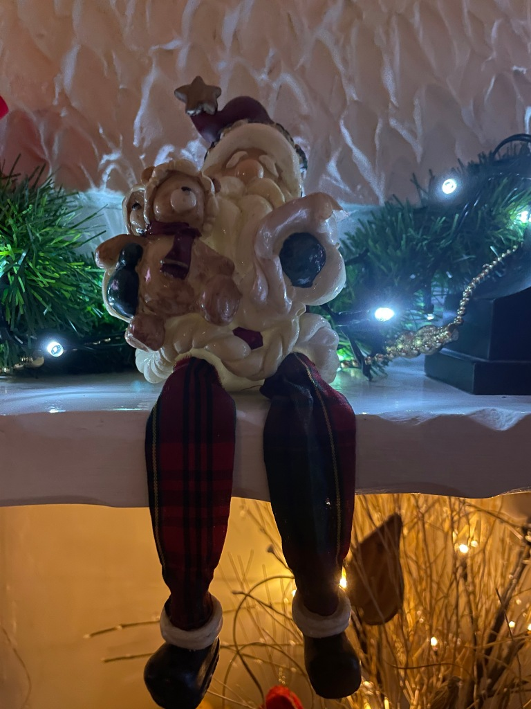 A Father Christmas is sat on the fireplace, his legs are dangling down.