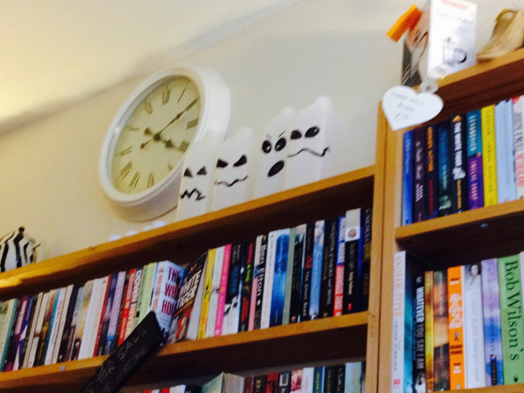 Looking at a  book shelf, there isa clock on the all above.
